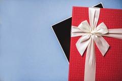 Раскройте красный цвет присутствующий с смычком на голубой предпосылке Стоковое Изображение RF