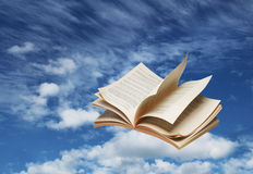 Раскройте летание книги на голубом небе Стоковая Фотография RF