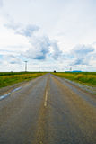 Раскройте дорогу под облачным небом между полями солнцецвета Стоковая Фотография