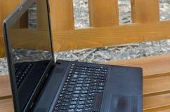 Раскройте портативный компьютер на деревянной скамье стоковое изображение rf