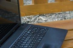 Раскройте портативный компьютер на деревянной скамье стоковая фотография
