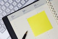 Раскройте пустой дневник с желтыми липкими примечаниями и ручку аранжированную на клавиатуре стола офиса Стоковое Изображение