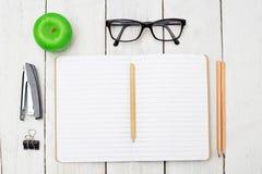 Раскройте тетрадь для примечаний, канцелярских принадлежностей и зеленого яблока на woode Стоковое Изображение