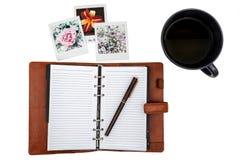 Раскройте тетрадь с ручкой, пары поляроидных изображений и чашку чаю Стоковое Изображение