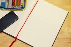 Раскройте тетрадь с чашкой кофе и покрашенными карандашами, на деревянном столе скопируйте космос стоковые изображения