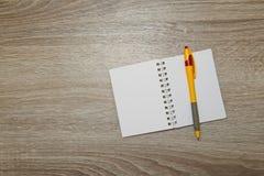 Раскройте тетрадь и пишите на деревянной таблице офиса Взгляд сверху с космосом экземпляра Стоковое Фото