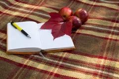 Раскройте тетрадь и пишите на шотландке с яблоками и листьями красного цвета Стоковые Изображения