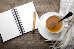 Раскройте тетрадь и чашку чаю Стоковые Изображения