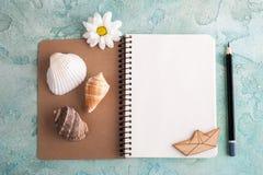 Раскройте тетрадь, карандаш, раковины моря, деревянную шлюпку Стоковое Фото
