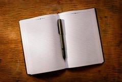 Раскройте тетрадь на ручке таблицы и шариковой авторучки Стоковые Фотографии RF