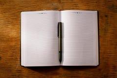 Раскройте тетрадь на ручке таблицы и шариковой авторучки Стоковое фото RF