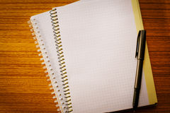 Раскройте тетрадь на ручке таблицы и шариковой авторучки Стоковая Фотография