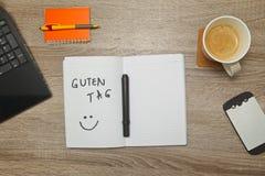 Раскройте тетрадь с добрый день немецкого ` БИРКИ ` GUTEN текста и чашку кофе на деревянной предпосылке Стоковое Фото