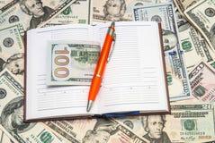 Раскройте тетрадь с предпосылкой долларов Стоковое Изображение