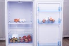 Раскройте холодильник, яичка, груши и яблока на полке холодильника Стоковые Изображения