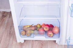 Раскройте холодильник, яичка, груши и яблока на полке холодильника Стоковая Фотография