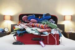 Раскройте чемодан на кровати Стоковая Фотография RF