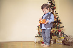 Раскрывать мальчика присутствующий перед рождественской елкой Стоковое фото RF