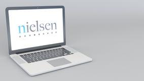 Раскрывая и закрывая компьтер-книжка с логотипом удерживаний Нильсена перевод 4K редакционный 3D Стоковая Фотография