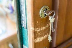 Раскрытая бронированная дверь с keychain в замке Поцарапанная деревянная часть под пуком ключей стоковое фото