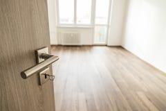 Раскрытая деревянная дверь с серебряной штейновой ручкой Стоковая Фотография