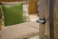 Раскрытая деревянная дверь к спальне с зеленой подушкой на кровати стоковые изображения rf