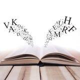 Раскрытая книга на деревянном столе против белой предпосылки с письмом стоковое фото