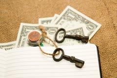 Раскрытая тетрадь, ключ и деньги на старой ткани Стоковые Фотографии RF