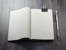 Раскрытая тетрадь с прописями с черной ручкой зажима и серебра перевод 3d бесплатная иллюстрация
