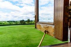 Раскрытое деревянное Windows для зеленых поля и неба Стоковая Фотография RF