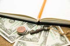 Раскрытые тетрадь, карандаш, ключ и деньги на старой ткани Стоковое Изображение
