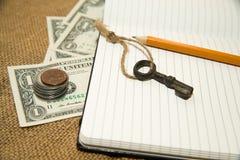 Раскрытые тетрадь, карандаш, ключ и деньги на старой ткани Стоковое фото RF