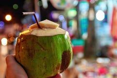 Раскрытый зеленый молодой кокос с трубкой для коктеиля на предпосылке рынка ночи светов Экзотическое питье, здоровое молоко кокос Стоковая Фотография