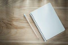 Раскрытый карандаш тетради с прописями на деревянной доске Стоковое Изображение