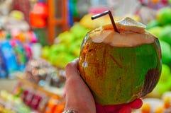 Раскрытый кокос с трубкой для коктеиля на предпосылке светов рынка ночи Экзотическое питье, здоровое молоко кокоса Стоковые Фото