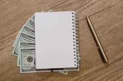 Раскрытый пустой блокнот с ручкой и долларом Стоковые Фотографии RF