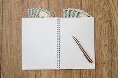 Раскрытый пустой блокнот с ручкой и долларом Стоковая Фотография