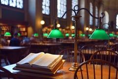 Раскрытый словарь и классическое бронзовое lampstand на деревянной таблице стоковая фотография rf