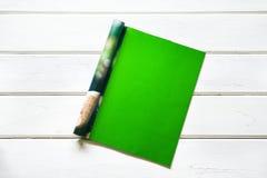 Раскрыл пустую насмешку зеленого цвета вверх по странице кассеты на белых деревянных животиках Стоковое Фото
