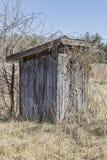 Распадаясь уборная во дворе в сельском районе стоковое изображение