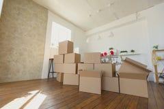 Распаковывающ коробки в новых домашних и кладя вещах прочь в кухне, большие картонные коробки в новом доме Двигать к новой концеп Стоковые Фото