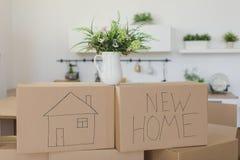 Распаковывающ коробки в новых домашних и кладя вещах прочь в кухне, большие картонные коробки в новом доме Двигать к новой концеп Стоковое Фото