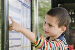Расписание чтения ребенка на автобусной остановке стоковое изображение