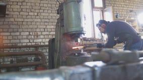 Расплавленный метал обработан под давлением в руках кузнеца, широкоформатных стоковое фото