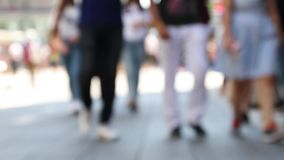 Расплывчатая предпосылка толпы Предпосылка запачканная отснятым видеоматериалом толпы людей идя на улицу акции видеоматериалы