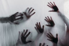 расплывчатые страшные силуэты человеческих рук касаясь матированному стеклу стоковое фото rf