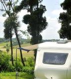 Располагаться лагерем во Франции с караваном между деревьями стоковое изображение