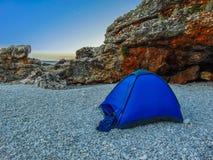 Располагаясь лагерем шатер около пляжа перед пещерой стоковое фото rf