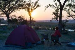 Располагаясь лагерем шатер, стулья и оснащение для кемпинга Восход солнца над граница рекой Okavango, Намибией Ботсваной Путешест Стоковое Изображение RF
