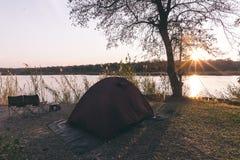 Располагаясь лагерем шатер, стулья и оснащение для кемпинга Восход солнца над граница рекой Okavango, Намибией Ботсваной Путешест Стоковая Фотография